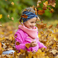 Young girl enjoys playing with autumn leaves