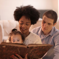 Child with parents, reading a book