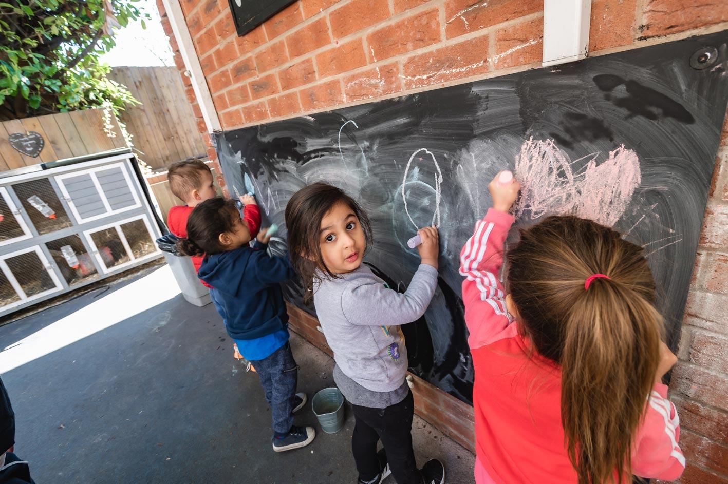 Nursery children enjoying marking activities on a blackboard in our outdoor play area.