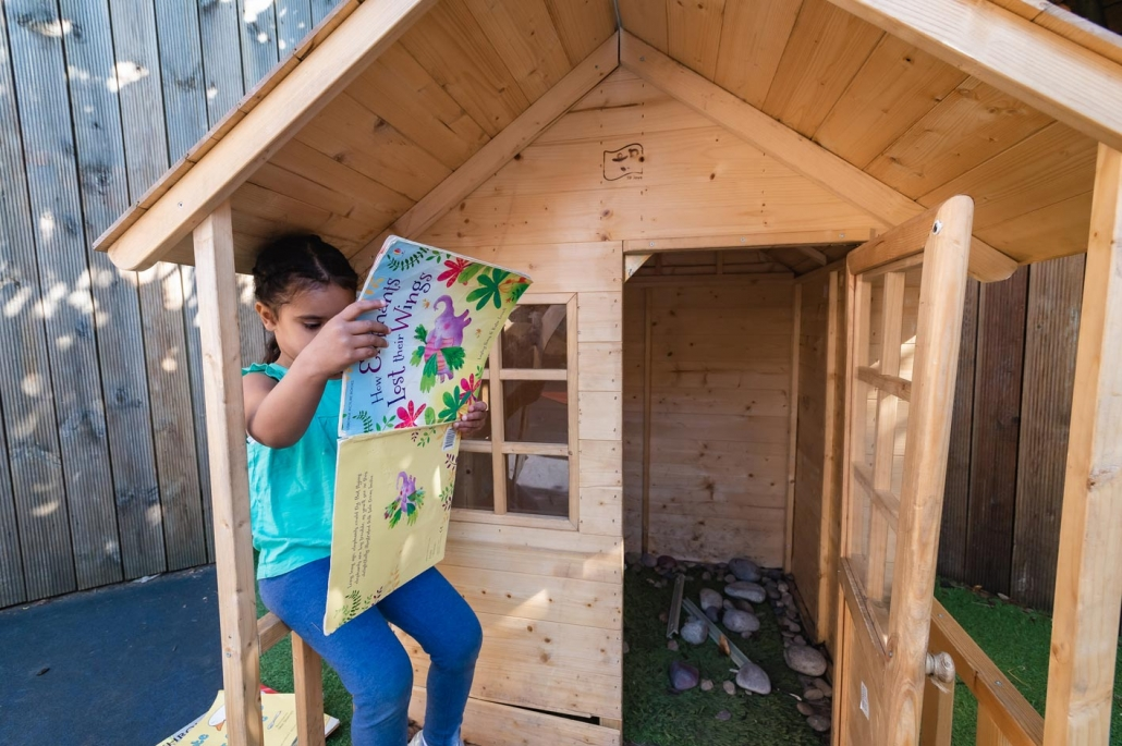 One of our under-five girls reads outside the summer house.