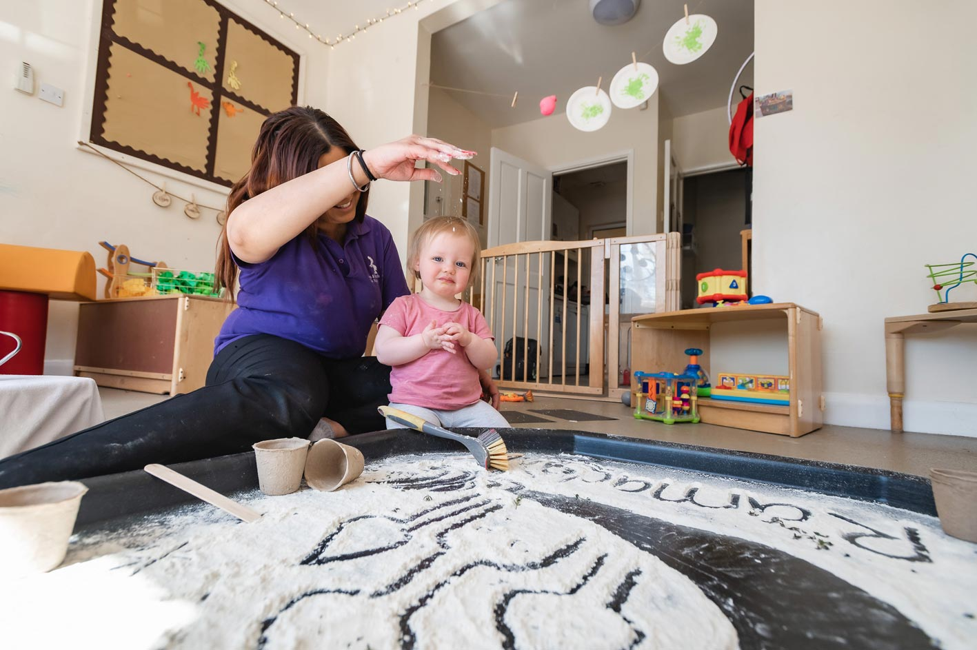 A childcare professional helps an under-five learn through messy play.